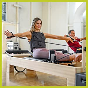 2 people in studio sitting up on Pilates Reformer w/ legs forward and arms extended in straps.