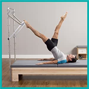 Man on Reformer w/ legs and torso extended above with leg up on tower bar and arms flat on carriage.