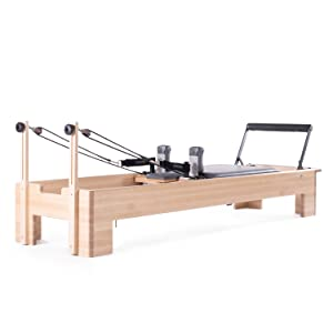 Studio Reformer on a white background prominently featuring the straps, handles, and maple frame.